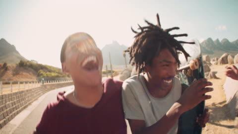 vídeos y material grabado en eventos de stock de patinadores reír juntos al aire libre, con monopatines en la mano - actividades recreativas