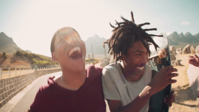stockvideo's en b-roll-footage met skateboarders lachen samen, buiten, met skateboards in hand - friends