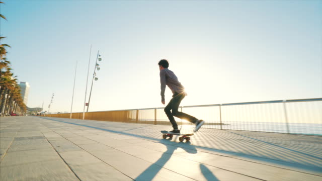 Skateboarding near the beach. Young man enjoying skateboarding in a beautiful sunny day. skateboarding stock videos & royalty-free footage