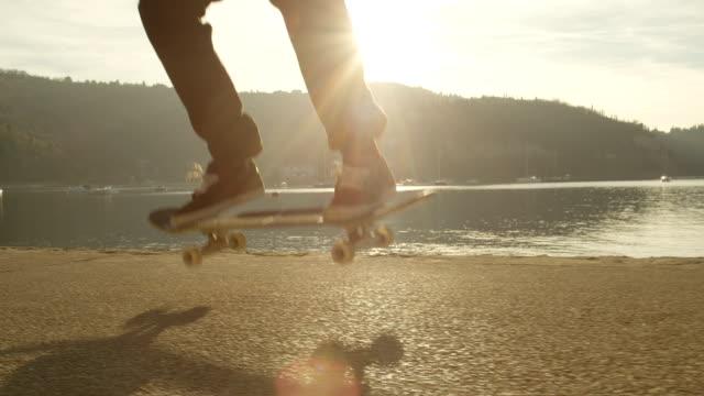 slow motion close up: skater jumping spinning skateboard in the air at sunset - łyżwa filmów i materiałów b-roll