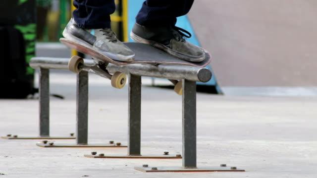 skater stellen schleifen trick schwach auf der schiene im skatepark, nahaufnahme in slowmotion - grind stock-videos und b-roll-filmmaterial