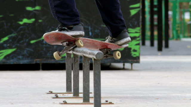 Skater make grind trick smith on rail in skatepark, close-up view in slowmotion
