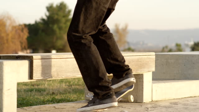 SLOW MOTION, CLOSE UP: Skater performing jumping tricks and sliding on the bench video