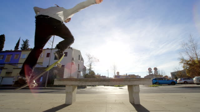 SLOW MOTION, CLOSE UP: Skater performing tricks jumping and sliding on the bench video