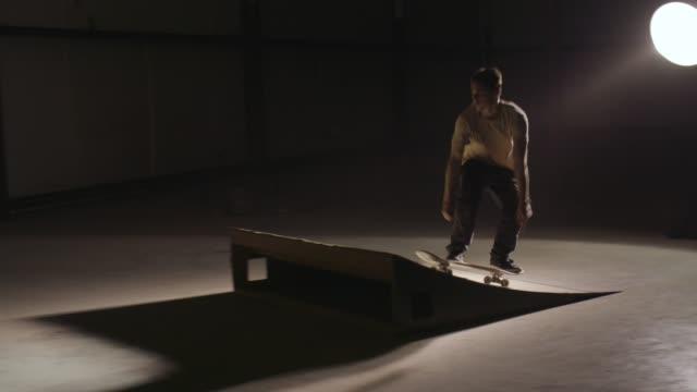 stockvideo's en b-roll-footage met skater silhouet in leeg pakhuis dat grote truc van het skateboard doet - 25 29 jaar