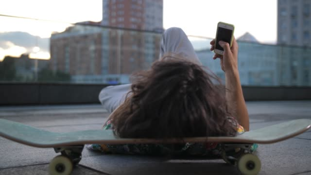 skater surfing on phone lying with head on board - instagram filmów i materiałów b-roll