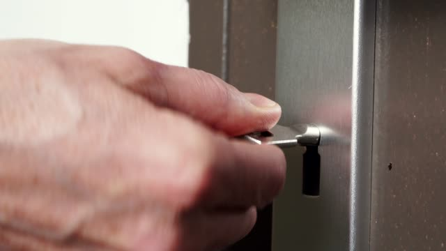 Skeleton key going into old keyhole lock 4K The key is inserted into keyhole of old wooden door and open or close. Home safety and security. 4K ProRes HQ codec keyhole stock videos & royalty-free footage