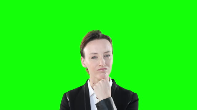skeptical caucasian woman looking at camera on green background. - direttrice video stock e b–roll