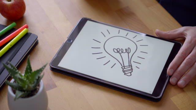 Sketching a Lightbulb for Creativity Designer drawing a light bulb on a digital tablet using a stylus pen. table top view stock videos & royalty-free footage