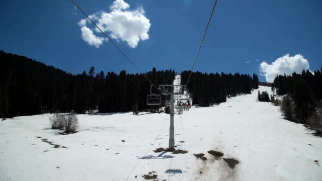 Ski chair-lift with skiers in snow-capped mountains video