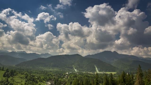 bulutlu bir günde kayakla atlama ve giewont dağı, zakopane, polonya, timelapse, 4k - zakopane stok videoları ve detay görüntü çekimi