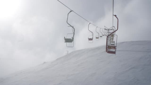 Ski lift chairs going up a mountain in bad weather in the Caucasus Mountains