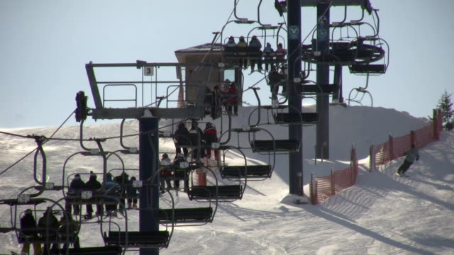 Ski lift slowly transports people to the top (High Definition) video