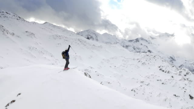 AERIAL Ski tourer raising hands on the conquered mountain top video