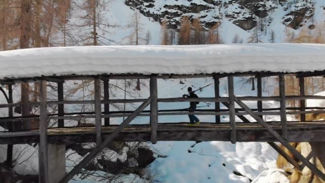 Ski touring in the Italian Alps: Crossing the bridge with ski on shoulders