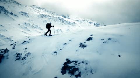 AERIAL Ski touring over the mountain ridge Aerial shot of a ski tourer walking on the mountain ridge. Shot in Slovenia, Europe determination stock videos & royalty-free footage