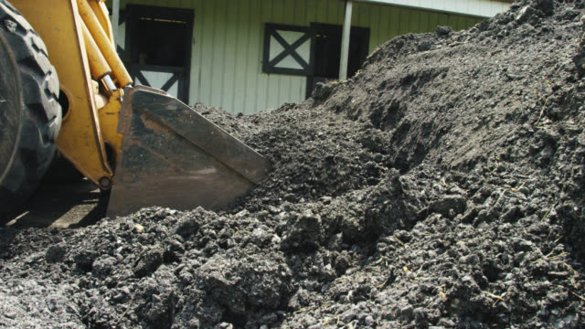 a skid-steer pushes and spreads asphalt around a new driveway in preparation for paving outside a horse barn on a partly cloudy day - ghiaia video stock e b–roll