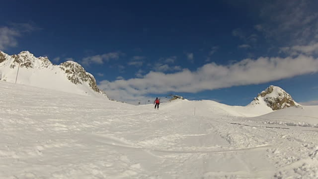 Skier carving and spraying snow at camera, real time video
