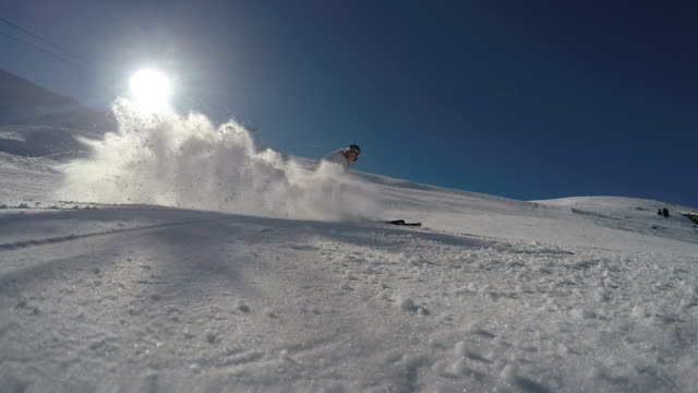 Skier carving and spraying snow at camera, slow motion video