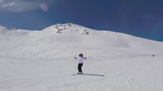 skier skiing down the mountainside and raises his hands up portray success - sci attrezzatura sportiva video stock e b–roll