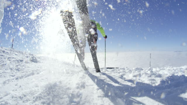 slow motion skier starts to ski on a sunny winter day at the top of the mountain - sci attrezzatura sportiva video stock e b–roll