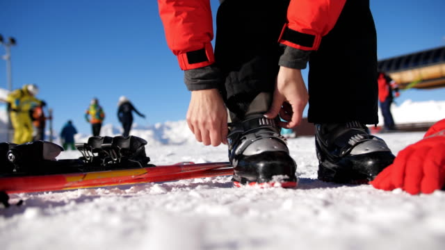 skier stepping into the ski bindings with his ski boots on a sunny morning. - sci sci e snowboard video stock e b–roll