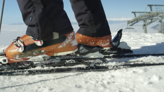 SLOW MOTION CLOSE: Skier steps in ski bindings with ski boots at resort in Alps