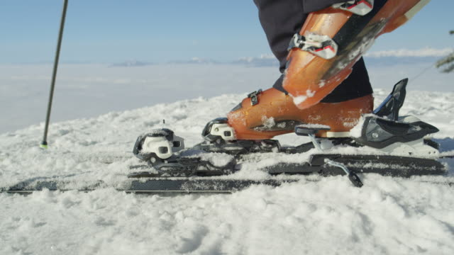 slow motion close: skier steps into the ski bindings with ski boots on the piste - sci video stock e b–roll