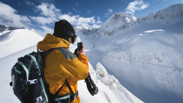 Skier taking video with smart phone on top of mountain
