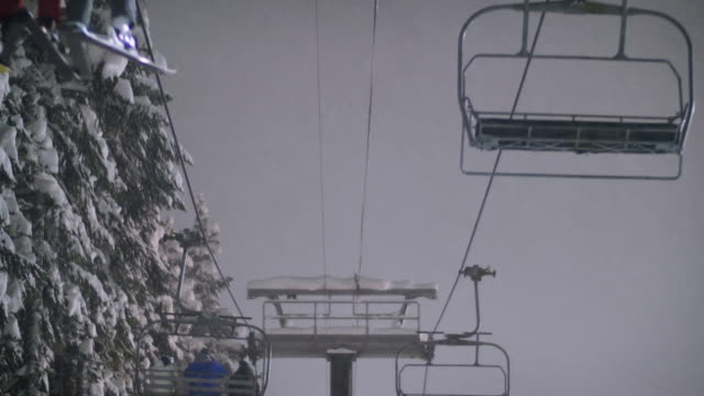 Skiers and Snowboarders Riding Chairlift with Heavy Snow Falling at Night video