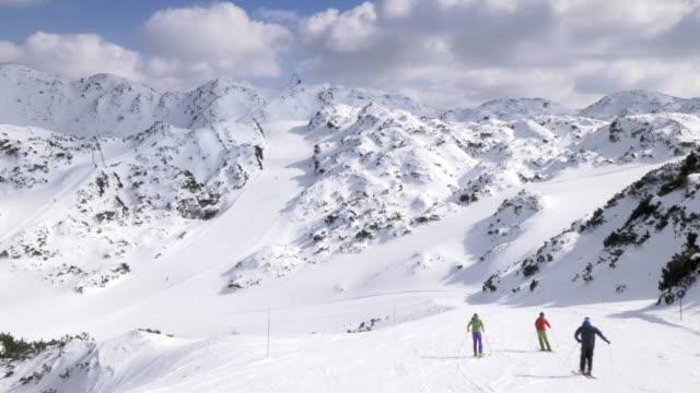 aerea sciatori carving lungo le piste da sci in giornata di sole - sci sci e snowboard video stock e b–roll