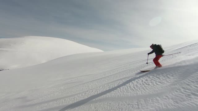 skiers descending mountain in deep snow powder - sci video stock e b–roll