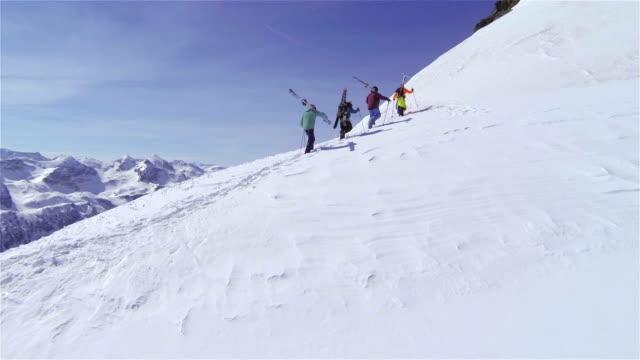 veduta aerea: sciatori trekking in salita, per trasportare gli sci - rappresentazione umana video stock e b–roll