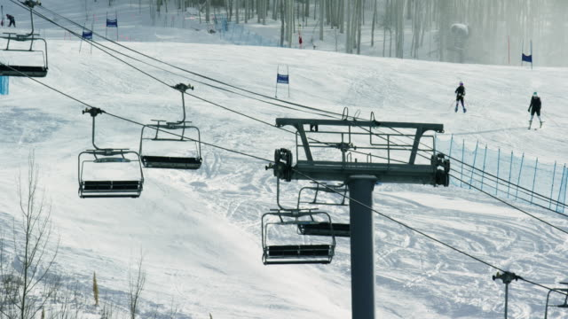 Skiers Ride a Ski Lift while People Ski the Slopes in the Background at a Colorado Mountain Ski Resort in Winter