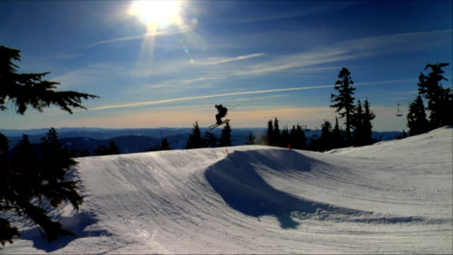 Skiiers jump into the horizon as sun sets (Two Clips) video