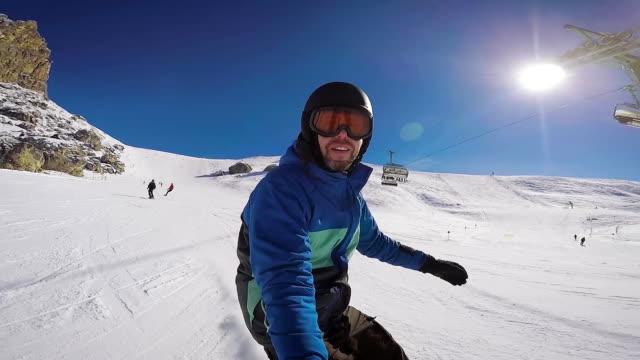 skidåkning i alperna på vintern. en man är rullande på en snowboard på snötäckta stigar av en skidort. killen tar sig själv på en extrem kamera - vintersport bildbanksvideor och videomaterial från bakom kulisserna
