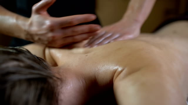Skill that revitalises A masseur putting her oiled hands on the naked back of a young woman that lying on the massage table and starting to massage her back, shoulder and arm massage oil stock videos & royalty-free footage