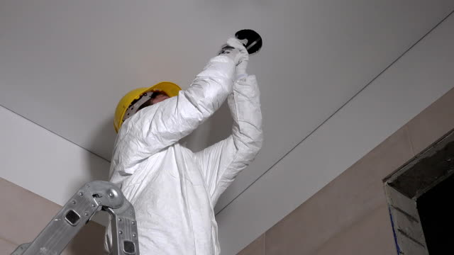 Skilled constructor man making plasterboard ceiling holes for light installation video
