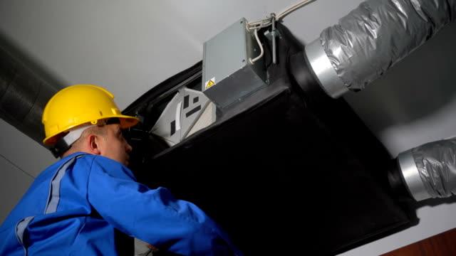 vídeos de stock, filmes e b-roll de engenheiro habilidoso removendo filtros do sistema de ventilação do ar - ar condicionado