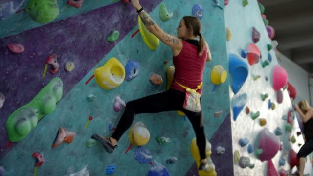 geschickte klettererin bouldern an der künstlichen wand - bouldering stock-videos und b-roll-filmmaterial