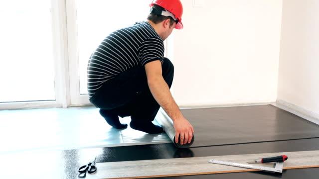 skicklig kille med röd hjälm låg sub-golv matta i ny lägenhet - construction workwear floor bildbanksvideor och videomaterial från bakom kulisserna