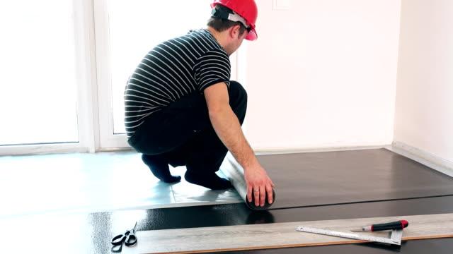 duktiga killen med den röda hjälmen låg sub golv matta i ny lägenhet - construction workwear floor bildbanksvideor och videomaterial från bakom kulisserna