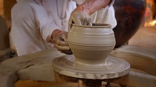Skilled hands of potter shaping the clay on potter wheel and sculpting clay pot jar. Shilpagram, Udaipur, Rajasthan, India