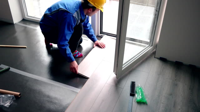 Skilled handyman guy with yellow hard hat installing laminate boards on floor video