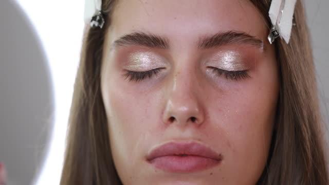 stockvideo's en b-roll-footage met bekwame make-up aanbrengen van oogschaduw op een jonge vrouw - oogschaduw