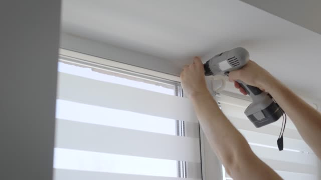 skilled man is spinning screw for fixing fastener on window, using recharged screwdriver in a room of modern apartment video