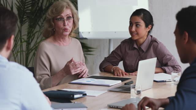 qualifizierte alte mentorin, die mitarbeiterinnen unterrichtet, führt unternehmensworkshop durch - grundschullehrer stock-videos und b-roll-filmmaterial