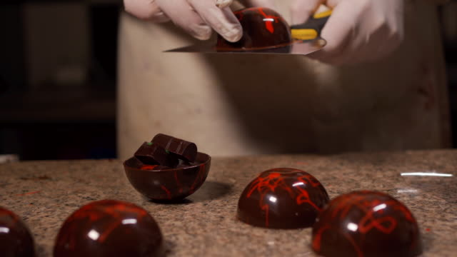 Skilled pastry baker making decorated chocolate spheres Skilled baker making chocolate spheres stuffed with chocolate bars on a kitchen counter. stuffed stock videos & royalty-free footage