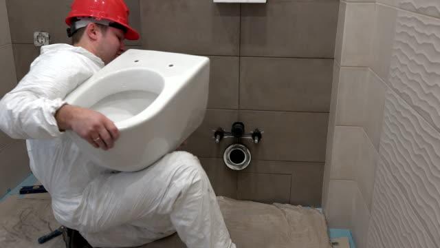 Skilled plumber man hanging heavy toilet bowl pan in new modern bathroom