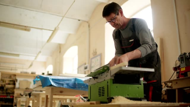 skilled professional carpenter using electric planing machine to plane wooden plank in his workshop, low angle medium shot - truciolo video stock e b–roll
